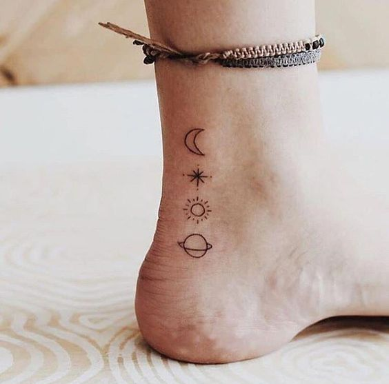 Small moon, planet, and sun tattoos on the foot