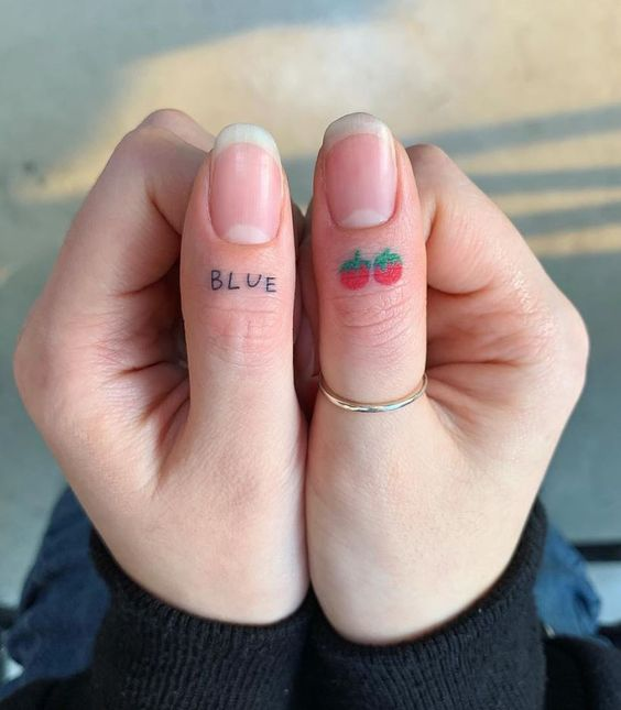 Tomato and blue tattoos on the fingers